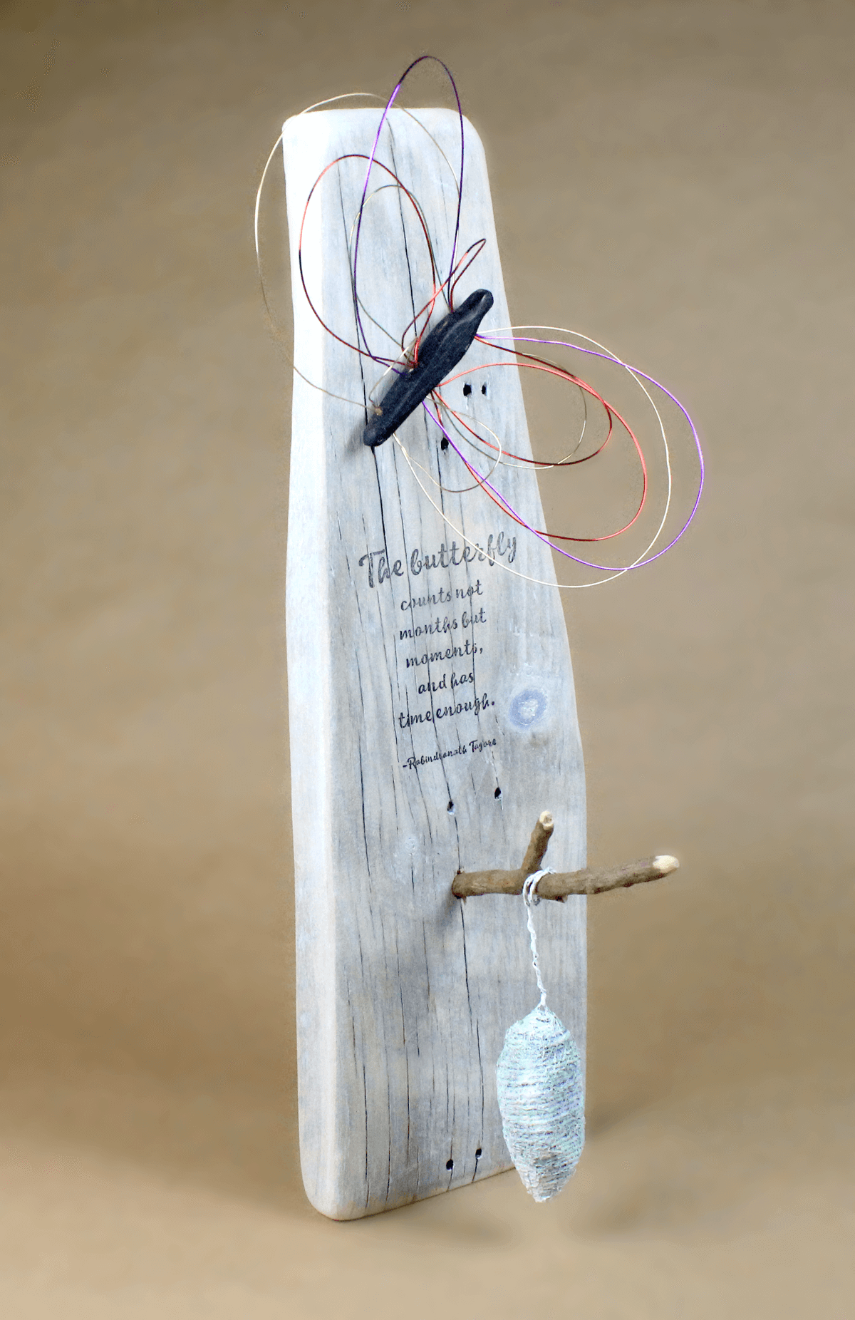Salvaged barn wood, wire, textile, acrylic paint and hand-stamped sculpture of a butterfly and a chrysalis on a twig.